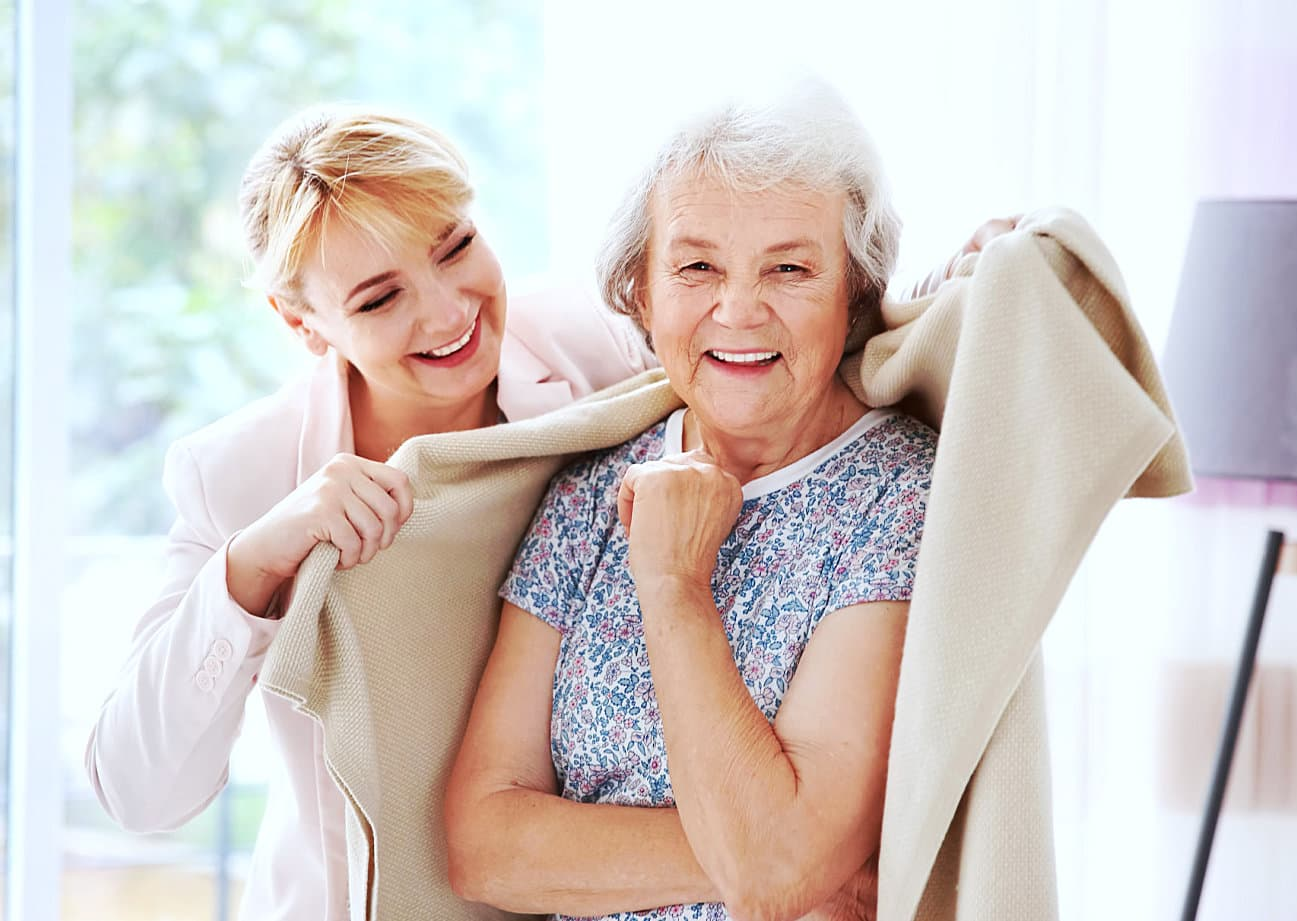 caregiver giving a blanket to senior woman