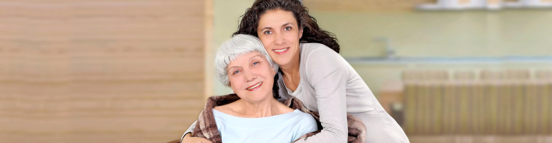 caregiver and senior woman are smiling while hugging
