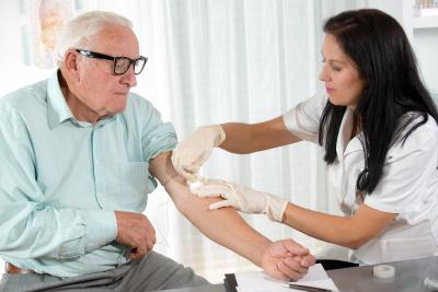 nurse with syringe is taking blood of senior man for test